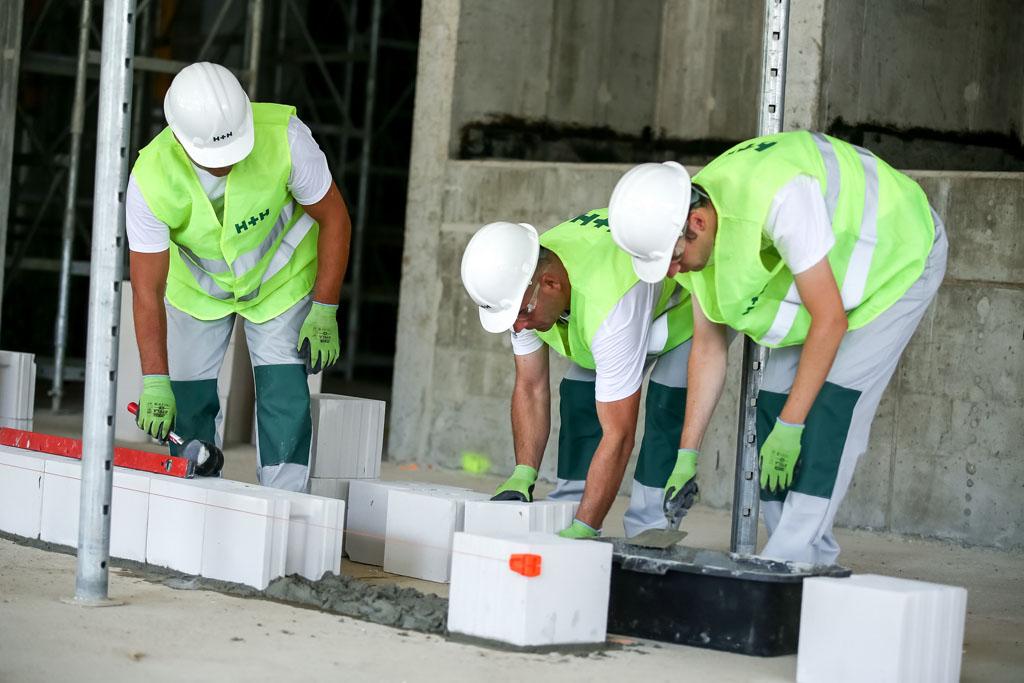 Murowanie pierwszej warstwy ściany nośnej z betonu komórkowego i bloczków silikatowych. Fot. H+H